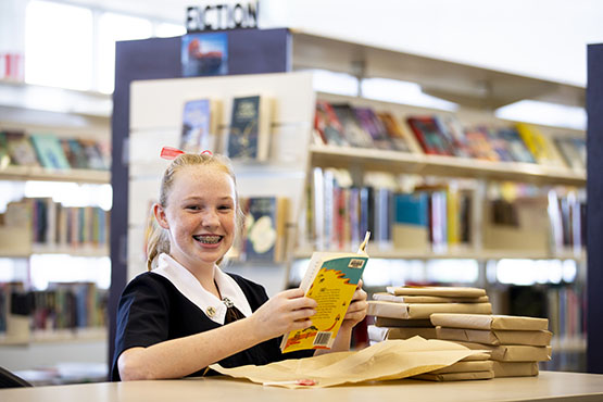 Year 8 St Margaret's Anglican Girls student Alayna Howells unwraps her book loan wrapped in brown paper and string as part of the school's Valentine's and Library Lovers' Day celebrations